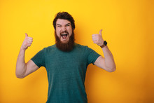 Portrait Of Excited Happy Bearded Man Showing Thumb Up Sign And Open Mouth Over Yellow Background