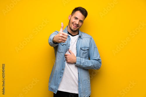 Fotografía  Handsome man over yellow wall with thumbs up because something good has happened