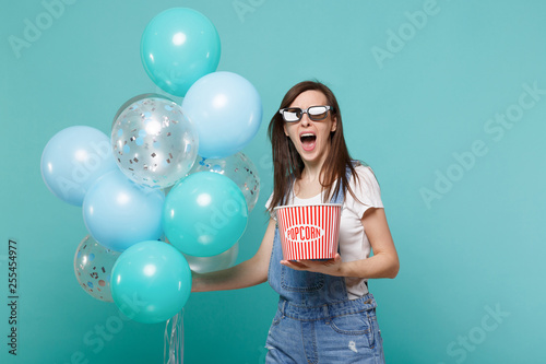 Photo Screaming girl in 3d glasses watching movie film hold bucket of popcorn celebrating with colorful air balloons isolated on blue turquoise background
