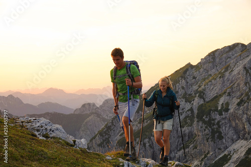 Fototapeta Hiker couple trekking up a grassy hill in the picturesque Alps at sunrise. obraz
