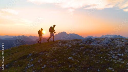 Fototapeta LENS FLARE: Carefree trekkers hiking uphill on a picturesque summer morning
