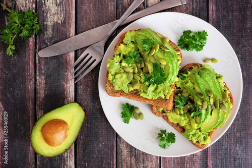 Photo Avocado toasts with pumpkin and chia seeds on whole grain bread