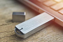 Close Up Of Metal USB Flash Drive Connected To Laptop On Wood Desk