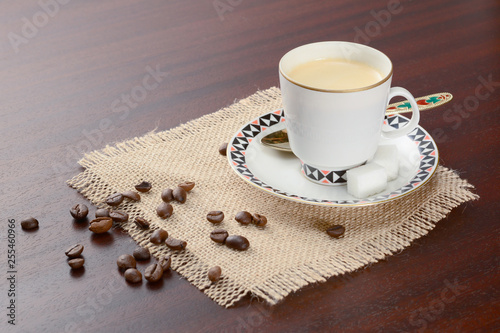 Fotografie, Obraz  Coffee in porcelain cup with saucer and golden spoon on a jute napkin