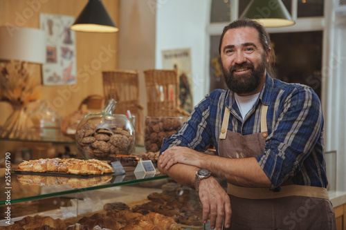 Papel de parede Handsome mature bearded male baker smiling to the camera proudly, working at his bakery shop, copy space