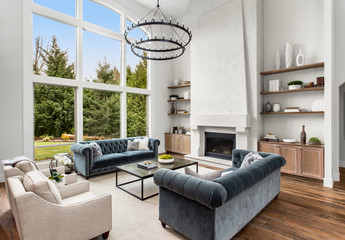 Beautiful living room in luxury home with tall ceiling, huge bank of windows, and floor to ceiling fireplace surround