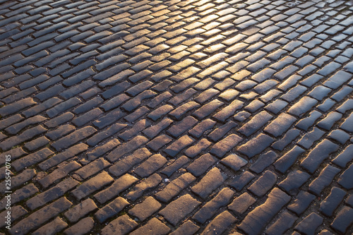 Fotografía Close up view of wet, dark and sunlit cobble paved street, Edinburgh