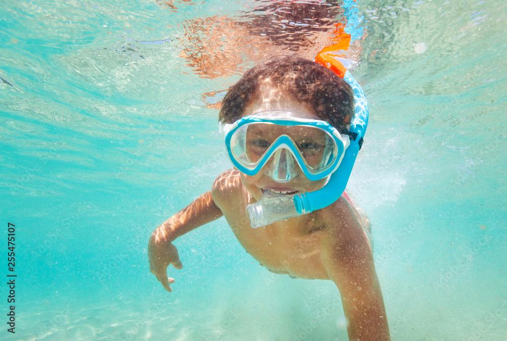 Fototapeta Happy kid boy snorkeling in clear blue sea