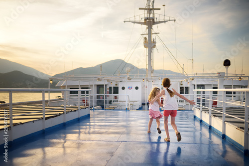 Adorable young girls enjoying ferry ride staring at the sea on sunset Wallpaper Mural