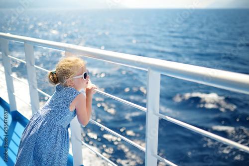 Fotografia  Adorable young girl enjoying ferry ride staring at the deep blue sea
