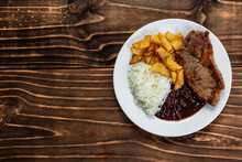 Meal On White Plate, Rice, Beans, Steak And Chips, Wooden Background