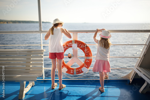 Foto Adorable young girls enjoying ferry ride staring at the sea on sunset