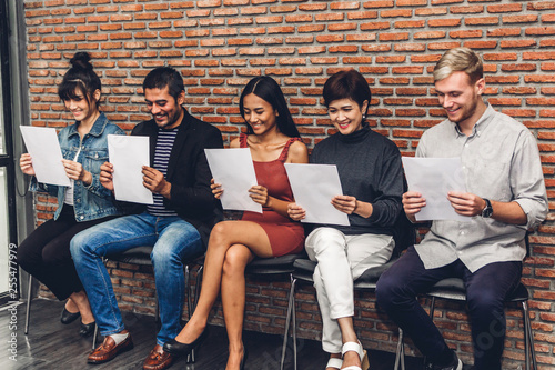Fototapety, obrazy: Group of business people holding paper while sitting on chair waiting for job interview against wall background