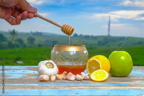 Photo  Fresh honey in glass jar , garlic, lemon and green apple on old wooden with blu