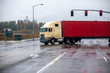 Old cab over big rig semi truck transporting container turning on the wet raining road with traffic light intersection