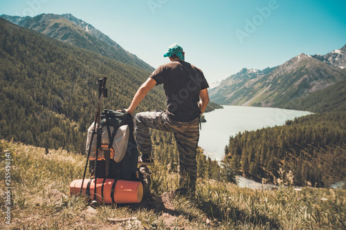 Foto  Standing sporty man with backpack on the mountain peak and beautiful mountains atbright sunny day