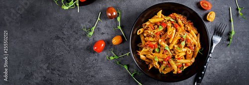 Fototapeta Penne pasta in tomato sauce with meat, tomatoes decorated with pea sprouts on a dark table. Top view. Banner obraz