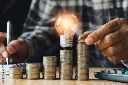 Fotografía  Business man putting coin with light bulb on table for saving bank and account for his money all in finance accounting concept