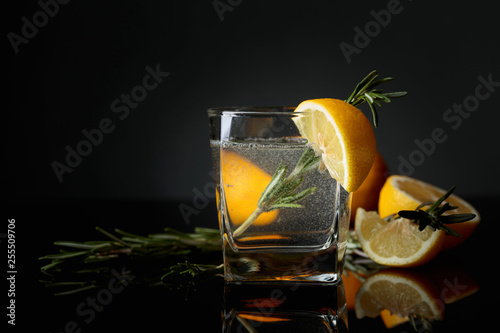 Fototapeta  Cocktail gin-tonic with lemon slices and twigs of rosemary.