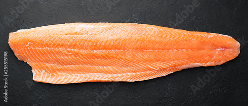 Fresh raw salmon fish steak on dark stone background. Fototapeta