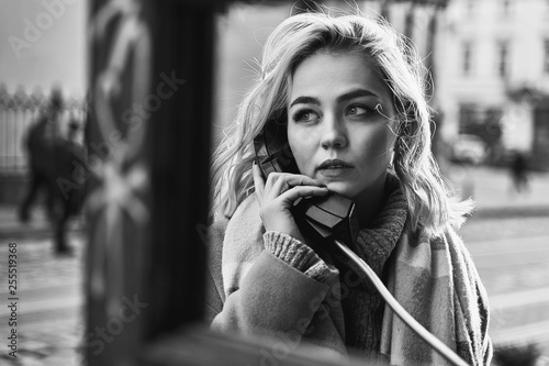 Obraz Young beautiful blond woman making an important call in a vintage public phone booth on a sunny evening - fototapety do salonu