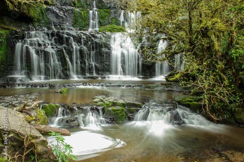 Photo Stands Dark grey Purakaunui Falls at The Catlins, South Island of New Zealand
