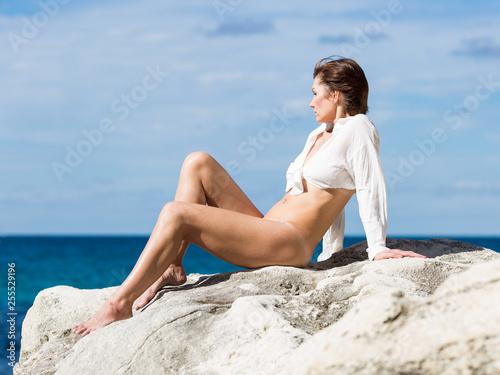 Fotografie, Tablou Female person resting on wild rocky seashore