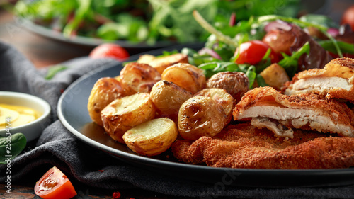 Fotografía  Homemade breaded pork schnitzel with roast potato and vegetables