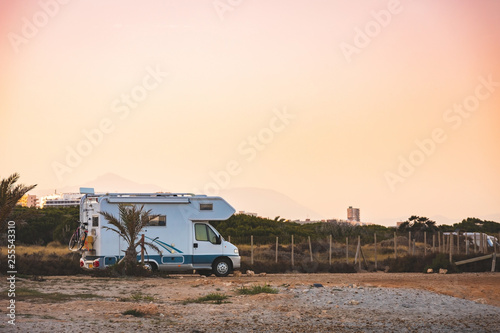 Motorhome making wild camp on the beach at a beautiful sunset or sunrise with mountains in the background Wallpaper Mural