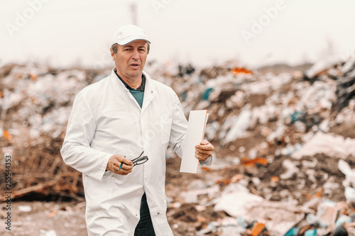 Valokuva  Ecologist in white uniform and cap on head holding clipboard and eyeglasses while walking on landfill