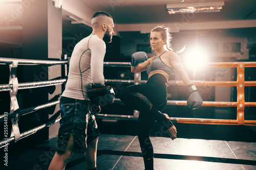Fotografía  Strong muscular boxer Caucasian woman kicking and having training in ring