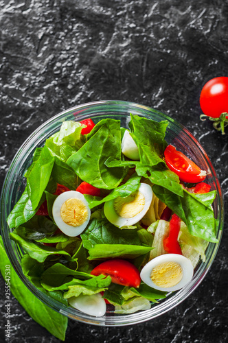 Fotografie, Obraz  spinach salad with eggs, pepper and tomatoes in glass bowl on dark background