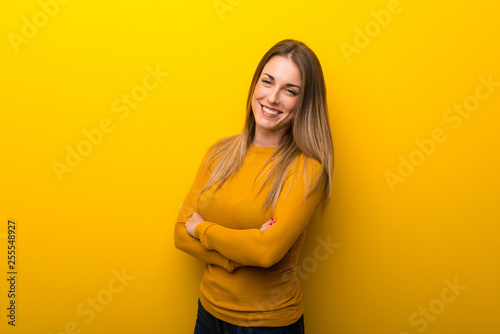 Fotografie, Obraz  Young woman on yellow background keeping the arms crossed in frontal position