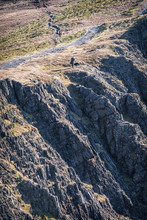A Lone Man And His Dog Next To Rocky Cliff On Blencathra, Lake District, Cumbria