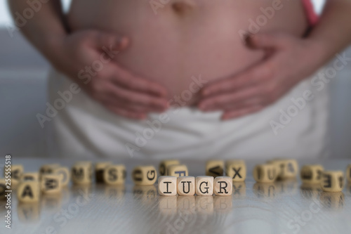 Fototapeta Abbreviation IUGR for intrauterine growth restriction composed of wooden letters