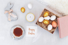 Easter Decoration. Nest With White And Gold Eggs In Pink Box, Decorative Bunny Figure Made Of Concrete, Candle, Cup Of Tea, White Fluffy Plaid And Card With Greeting Happy Easter On Grey Background.