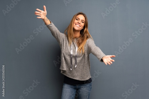 Photo  Blonde woman over grey background presenting and inviting to come with hand