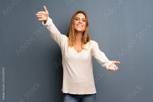 Fotografía  Blonde woman over grey background presenting and inviting to come with hand