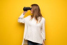 Blonde Woman Over Yellow Wall And Looking In The Distance With Binoculars