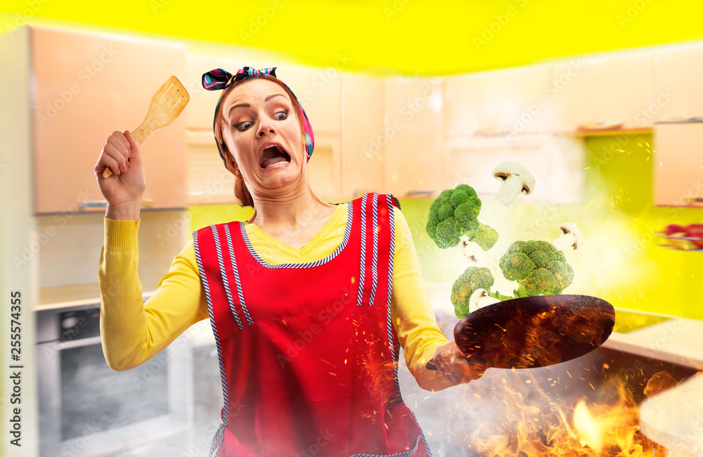 Fototapeta Crazy housewife in apron cooking broccoli on fire