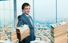 Young Businessman Holding Out A Wad Of Money