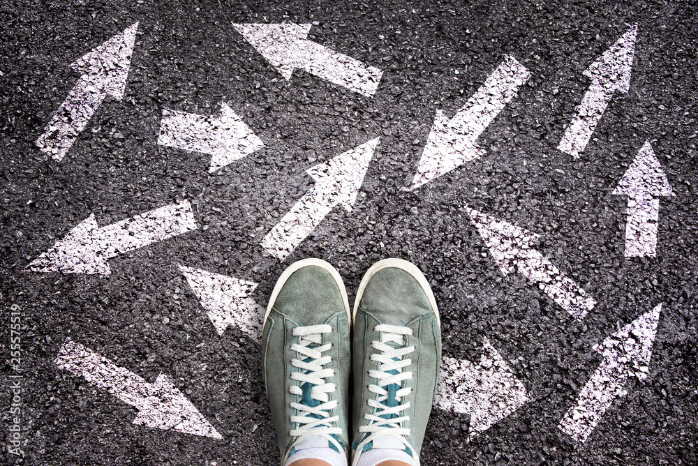 Fototapeta Sneaker shoes and arrows pointing in different directions on asphalt ground, choice concept