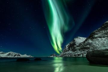 Piękne zielone zorza polarna na plaży Haukland na wyspach Lofoten w Norwegii