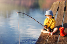 Boy On Wooden Dock With A Fishing Net