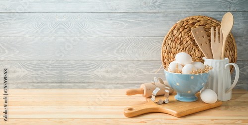 Easter baking background with eggs and kitchen utensils on wooden table Wallpaper Mural