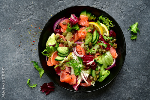 Leinwand Poster Vegetable salad with salted salmon in a black bowl