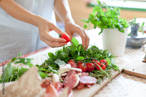 Obraz Woman is cooking in home kitchen. Female graceful hands hold cherry tomatoes and greens. Ingredients for preparing italian or french food are on table on wooden boards. Lifestyle moment. Close up. - fototapety do salonu