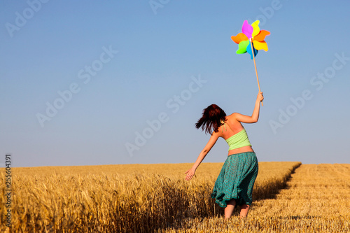 Vászonkép Young woman with pinwheel toy on wheat field.