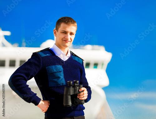 boatswain with binoculars near the boat. Wallpaper Mural