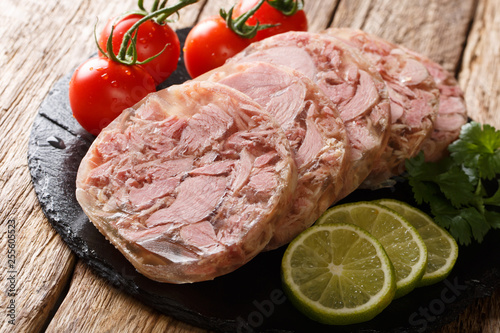Fotografia Homemade head cheese or brawn with fresh tomatoes, lime and cilantro close up